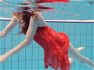 red clothed teenage swimming with her eyes opened